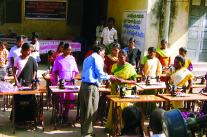 Photo of Sam Bandela presenting sewing machines to women in India courtesy CBF